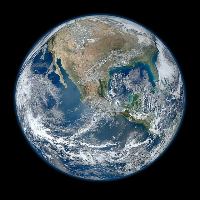 A planet of white cloud formations, brown and green land masses, and dark blue oceans.