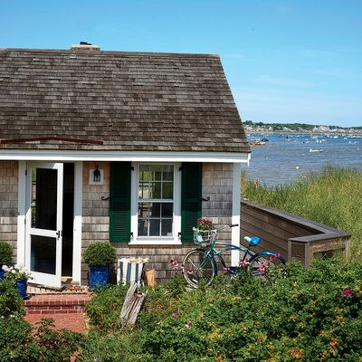 This charming 1930s cottage has all of the classic Cape Cod elements like cedar shingles and wood shutters. Its wraparound deck was expanded to welcome the family's summer guests. | Coastalliving.com