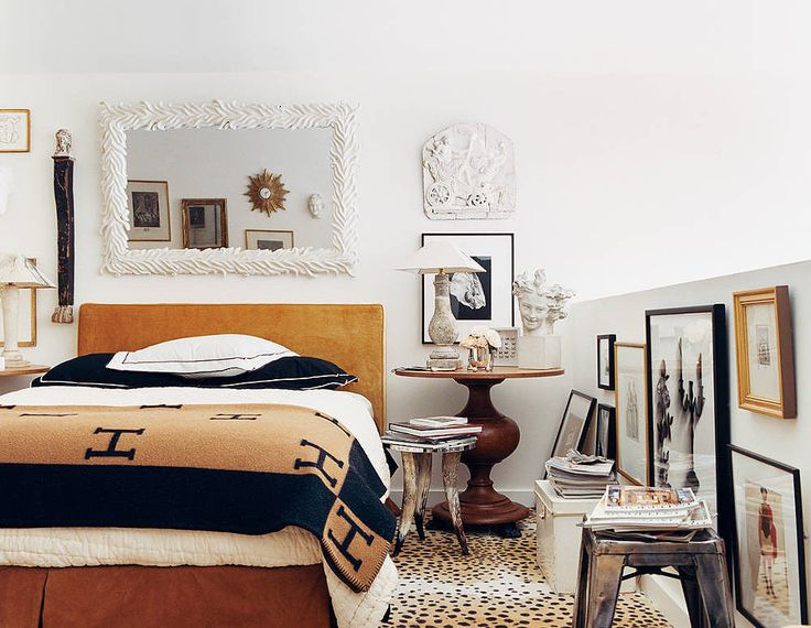 No headboard? No problem! A mirror makes a great substitute and helps to open up your room. Even if you have a headboard, hanging a mirror above it creates a gallery effect. But keep the mirror simple if you choose to pair the two . . .  Source: Domino
