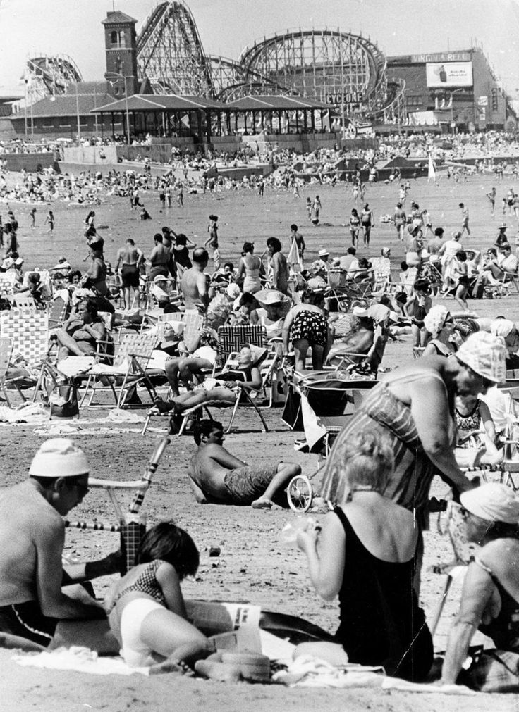 "July 8, 1968: The Cyclone, one of the largest roller coasters in the U.S., can be seen in the background as people sunbathed at Revere Beach. Built in 1925 by Harry Travers for 125,000 dollars, its cars traveled at a speed of 50 miles per hour and its climb reached a 100 feet. Leo Hurley, whose father and uncle started the amusement era on Revere Beach in 1898 and who ran the last rides before the amusement park closed in 1978, said Revere Beach was ""the Coney Island of Massachusetts"""