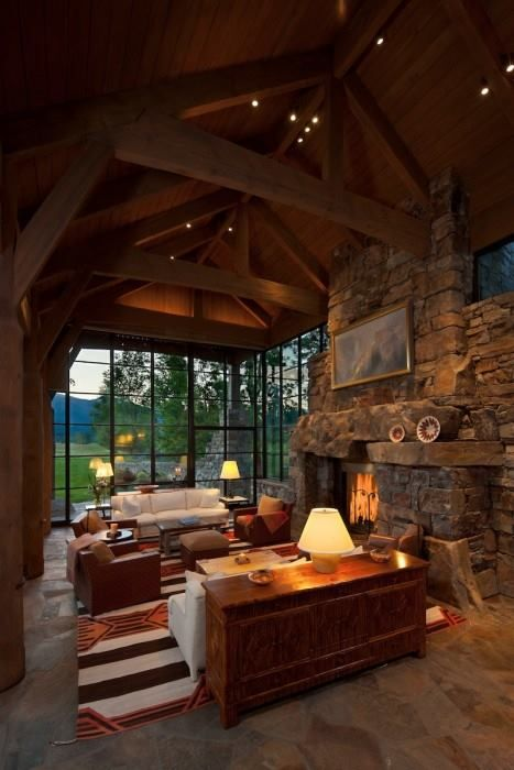 Vaulted ceiling living room with big windows and fireplace.