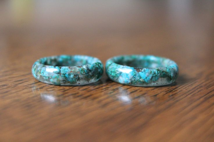 CHRYSOCOLLA RING This once polished piece of Chrysocolla was crushed and placed through an entire eco-epoxy resin ring.  SYMBOLIC DESCRIPTION Chrysocolla is a receptive stone, powered by the Moon with water. This tranquil energy helps with communication and meditation. It is used to banish fear and sadness while promoting peaceful feelings, allowing serenity and acceptance of change. Historically it was prescribed by magicians in protecting against nightmares, especially during travel .
