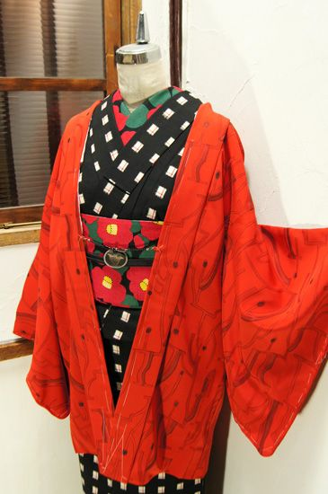 わずかに朱色みをおびた綺麗な赤の地に、枝付き燭台のようなモダンデザインが浮かび上がるレトロ羽織です。