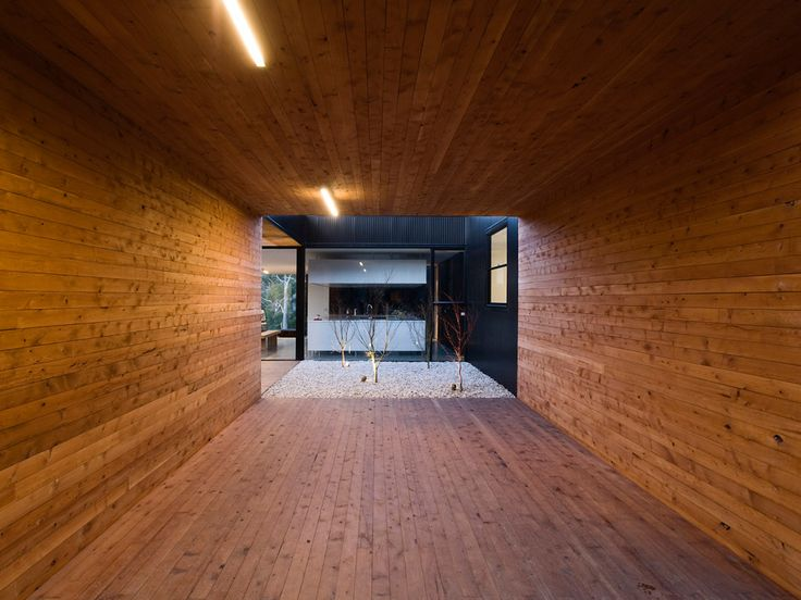 """Allens Rivulet House / Room 11 Architects. """"The building is conceived as a dark container in the landscape, a protective armour revealing a timber inner where outdoor activities take place within the confines of the building envelope""""."""