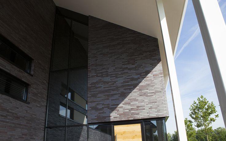 moderne woning | Een ruime moderne woning op De Scheifelaar voorzien van een imposante entree, grote overstekken en opvallend metselwerk met kenmerkende horizontale strookramen. De donkere kozijnen met stucwerk accenten dragen bij aan de moderne uitstraling.