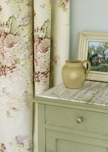 Side table painted in Chalk Paint® decorative paint by Annie Sloan. Colours chosen are Chateau Grey paired with Faded Roses fabric from the Annie Sloan Fabric Collection. On the table, a painting done by Karen of Classic Walls of New Jersey