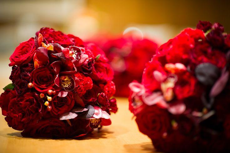 Red bridesmaids' bouquets with roses, cymbidium orchids, peonies and coxcomb {Evantine Design; Photo: Cliff Mautner}