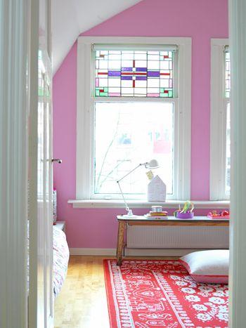 De kleuren roze en rood op deze slaapkamer zijn helemaal in stijl met het glas in lood van de ramen.