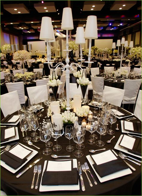 Flowers are a bit much, but I like the all white candelabras against the black table cloth