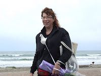 MickaCoo volunteer and pigeon rescuer Cheryl at the beach with her pet pigeon Mandee tucked happily in her jacket
