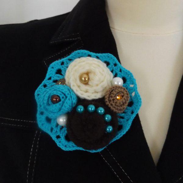 Romantikus hangulatú, vintage kitűző horgolt és textil virágokkal, valamint gyöngyökkel és gombokkal csipke alapon.
