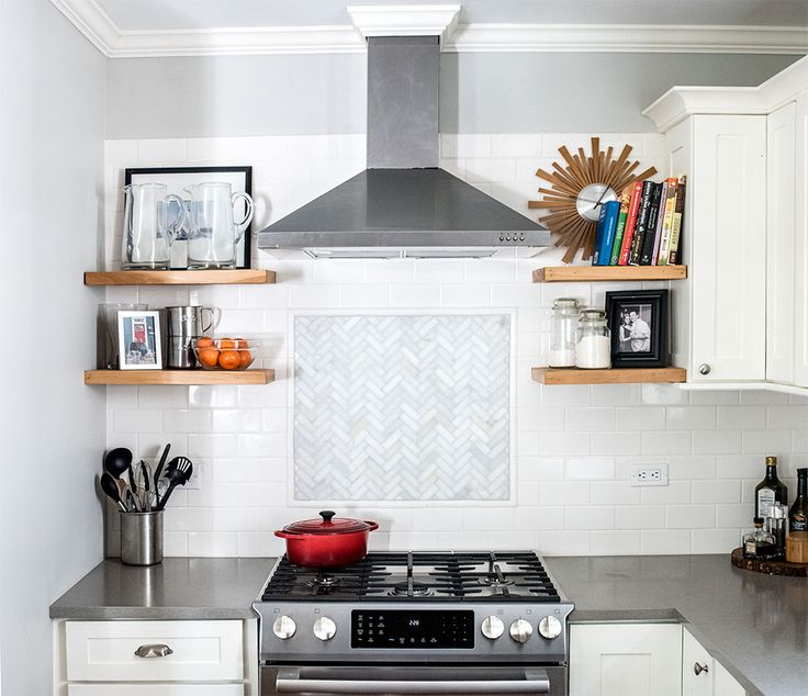 A crisp subway tile backsplash and marble basketweave accent above the Bosch kitchen range paired with a sleek hood from IKEA.