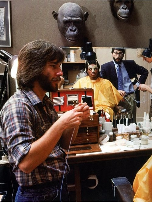 Michael Jackson getting his makeup work done by Rick Baker for his music video for 'Thriller' while director John Landis watches.