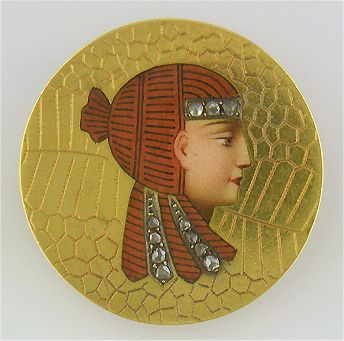An elegant Egyptian Revival brooch from the late Victorian era.  The brooch features a beautiful enamel portrait of an Egyptian noble woman or princess accented with eleven Rose-cut diamonds.  Crafted in 18kt gold, circa 1885.  jewelryexpert.com