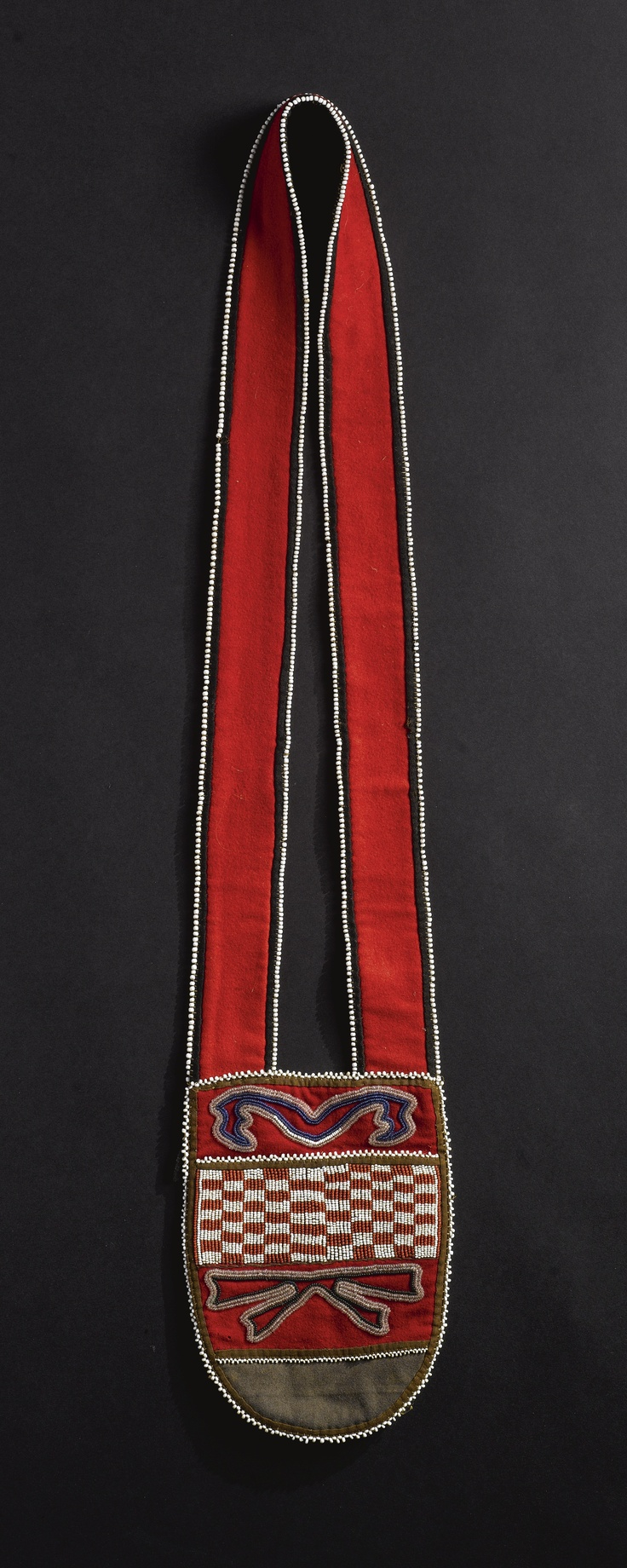 TALTAN BEADED CLOTH AND HIDE POUCH composed of a red stroud shoulder strap backed in commercial blanket cloth, an oval hide pouch suspended below, decorated with a loom-beaded panel in red and white glass beadwork, with rectangles, flanked by trade cloth applique with foliate designs. length with strap 29 1/2 in.