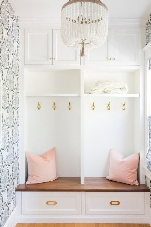 White and blue mudroom boasts a wall fitted with white cabinets adorned with shiny brass knobs as well as shelves stacked over open lockers lined with vintage brass hooks.