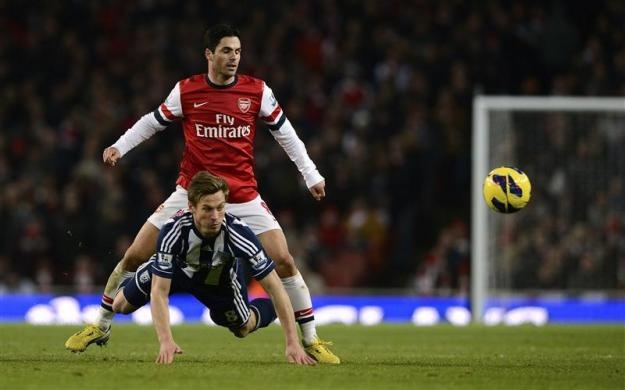 Arsenal's Mikel Arteta (top) challenges West Bromwich Albion's Markus Rosenberg during their English Premier League soccer match at the Emirates stadium in London December 8, 2012. REUTERS-Dylan Martinez
