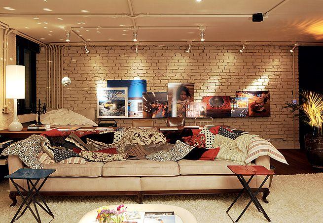 Neste apartamento, a superfície rústica da parede de tijolos e os tubos à vista, junto com os móveis antigos, aquecem o ambiente
