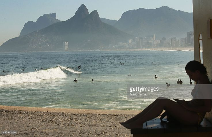 People surf at Ipanema beach, located outside Guanabara Bay, on August 3, 2015 in Rio de Janeiro, Brazil. The Rio government promised to clean 80 percent of the pollution and waste from neighboring Guanabara Bay, which will host sailing events, ahead of the Rio 2016 Olympic Games, but now admits that goal is inlikely to be reached. August 5 marks the one-year mark to the start of the Rio 2016 Olympic Games.