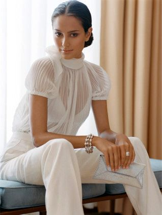 white sheer top and white pants with hair tied back. Classic