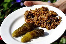 """""""Als Tscholent oder Tschulent (jiddisch: טשאָלנט, Aussprache: [ˈtʃolənt] oder [ˈtʃʊlənt], Hebräisch Chamin חמין, deutsch: heiß) wird im Ostjiddischen ein Eintopfgericht der aschkenasischen jüdischen Küche für die Mittagsmahlzeit am Schabbat bezeichnet, das am Freitag vor Schabbatbeginn zum Kochen gebracht und bei geringer Hitze bis zum Samstagmittag fertig gegart wird."""" Tscholent – Wikipedia"""