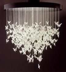 DIY chandelier - paper etc cutouts hung on strings under a drum shade.