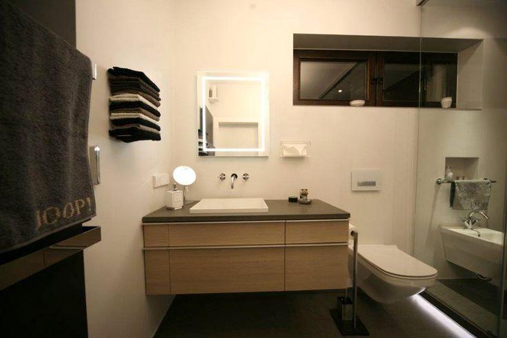 Waschtisch mit Holzfronten und Natursteinplatte, weißes Waschbecken mit Wandarmatur, darüber Spiegel mit Lichtrahmen