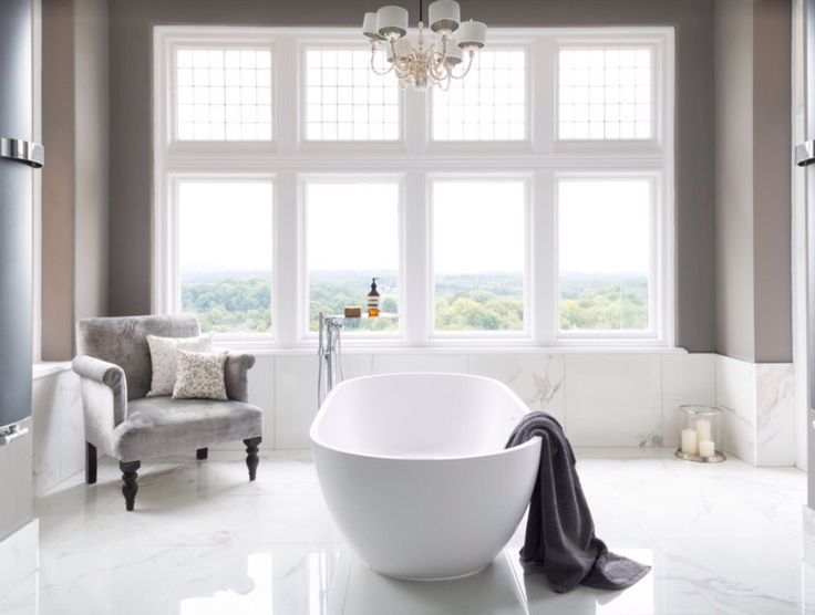 A beautiful traditional theme with crisp white and classic styling. The modern free standing bath is subtle in this spacious bathroom blending with the marble floor tiles.  Photo credit- Ripples Bathrooms