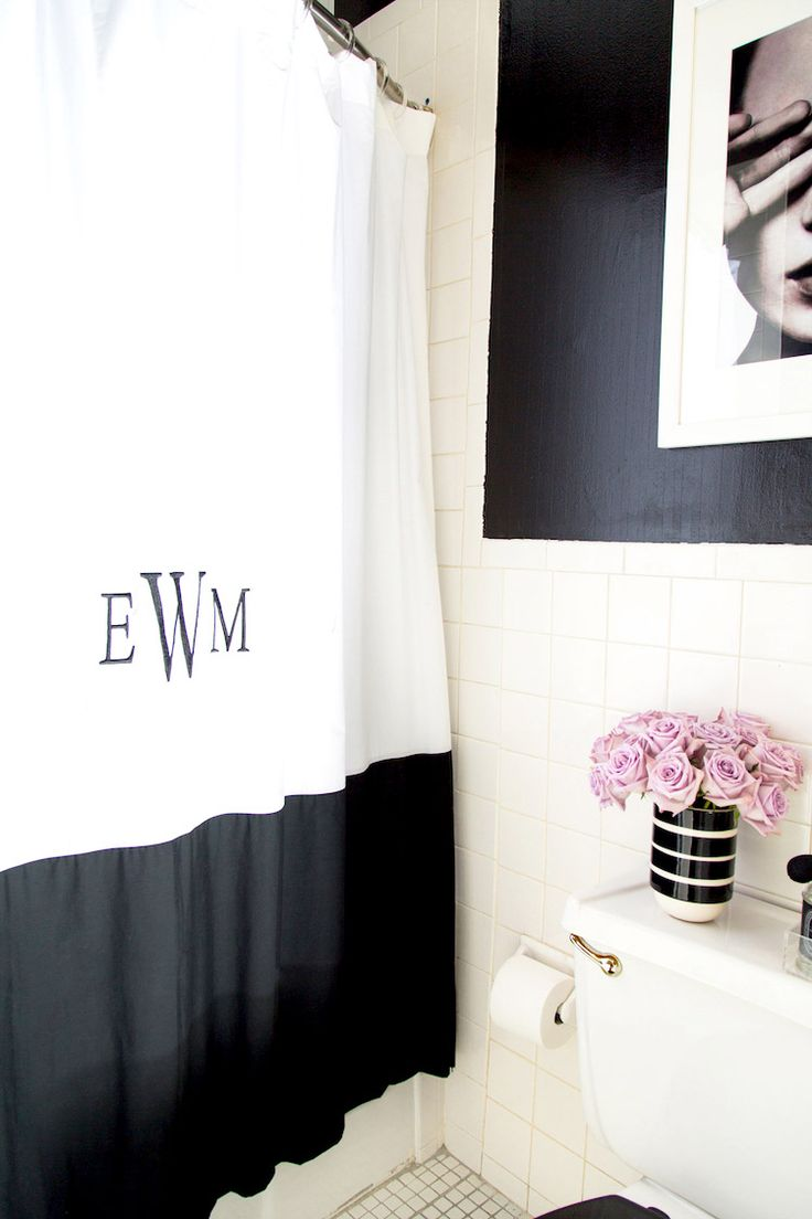 Monogrammed black and white shower curtains in bathroom with lilac roses