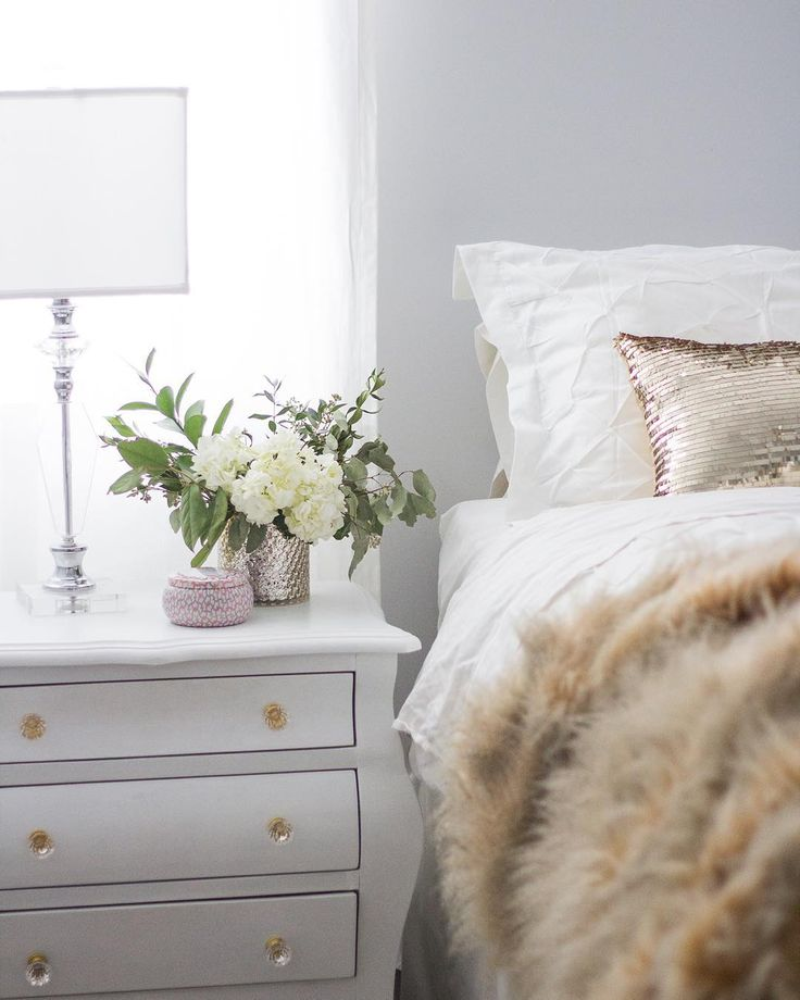 Gorgeous white bedroom with white bedding, sequinned pillow and faux fur throw.
