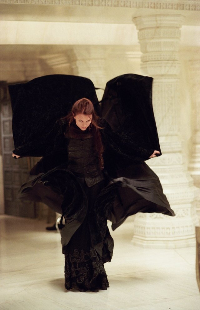 Mina Harker appearing to land as if from flight, with her black dress billowing out behind her