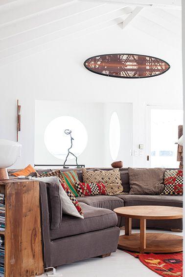 El living está marcado por la curva del sofá que cobra vida con almohadones de estampas africanas. Foto de Jesús Guiraud