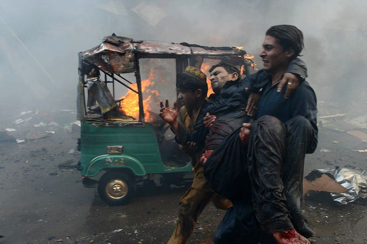 BOMBING AFTERMATH: A man carried another man who was injured when a bomb ripped through a busy market in Peshawar, Pakistan, Sunday, killing dozens of people. (Hasham Ahmed/Agence France-Presse/Getty Images)
