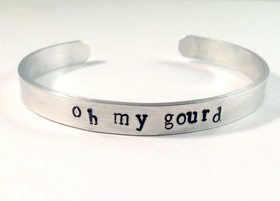 "Hand-stamped on a 1/4"" wide and 6 inches in length (prior to being bent) brush finished aluminum 14 gauge cuff. Pure aluminum does not tarnish and has a much lower rate of skin reaction than sterling silver. The font on this Oh my Gourd cuff bracelets is Bridgette lower. What is a Gourd? Its commonly used to describe crop plants in the family Cucurbitaceae, like pumpkins and squash. Adjustable for you: Gently pull apart to put on and gently squeeze to close. The bracelet fits a standard ..."