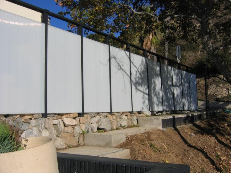 Polycarbonate panels and synthetic wood. Individual panels can be lighted for nighttime effects. http://www.designundersky.com/dus/2008/4/1/fence-concepts-formfunctionfun.html