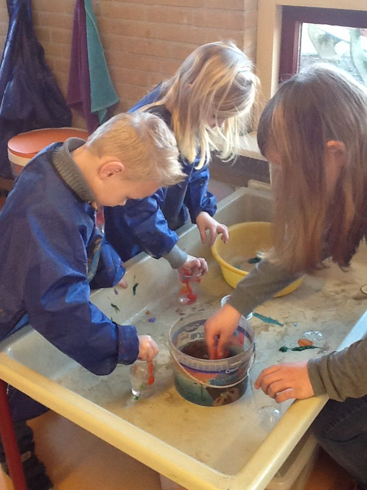 Samen heksendrankjes maken in de watertafel met crêpe-papier en water.