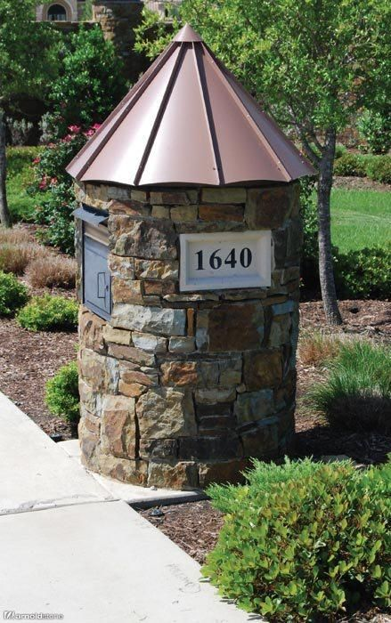 Round stone mailbox with copper roof.