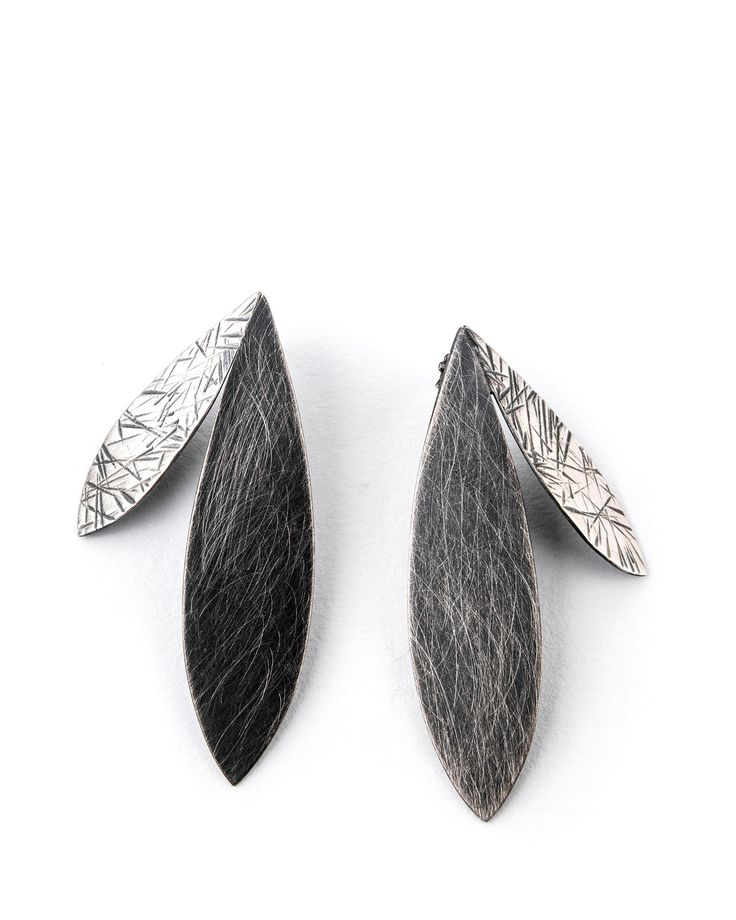 Large Double Feather Earrings by Linda Azar. Both architectural and organic, these handcrafted sterling silver earrings are rich with contrast: bright and oxidized finishes are paired with brushed and hammered textures for dramatic beauty. Sterling silver posts.