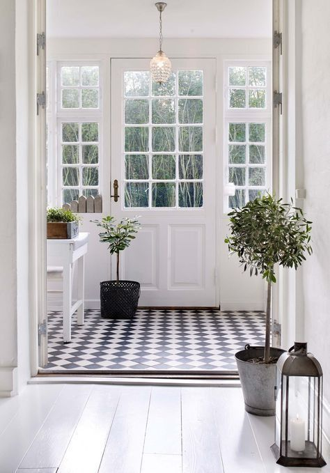 Classic black and white entryway with checkerboard floors and potted topiaries lining the hall.