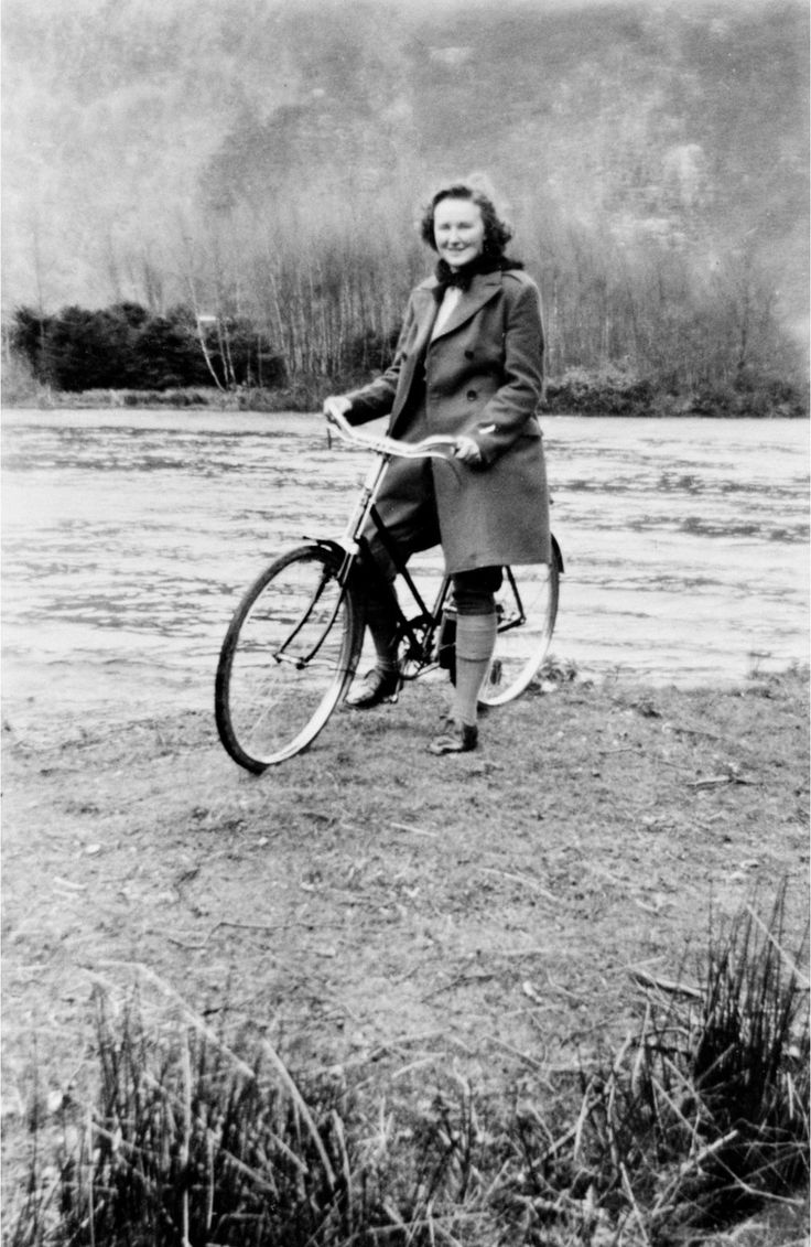 Jean Johnstone, a member of the Women's Timber Corps, posing with her bicycle beside Loch Eddy, Peebles