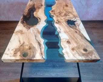 DEZE TABEL WORDT VERKOCHT  Rivier koffietafel gemaakt van oude massief hout. Gevuld met transparante epoxy hars en blauw transparant glas. Poten van metaal bedekt met een mat zwarte kleur. Het is uniek, een van een soort massief stuk hout. De unieke combinatie van boom ringen om het effect van de verscheidenheid van kleuren. Afmetingen: 98 x 84 cm en 40 cm hoogte (centimeters) 38, 5 x 33 in en 15,8 in hoogte (inch)  Contact over de verzendkosten voor de aankoop.  DEZE TABEL WORDT VERKOCHT