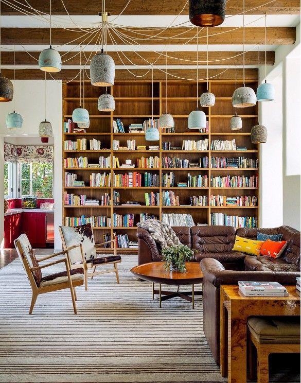 mid century living space full height bookshelves suspended lighting