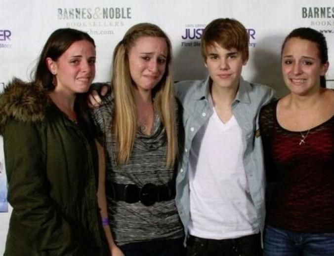 Non-Beliebers Justin Bieber posing with three crying girls