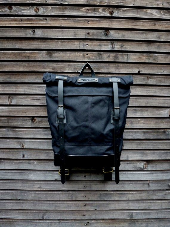 Black waxed canvas backpack with roll to close top and vegetable tanned leather shoulderstrap,handle and leather bottem COLLECTION UNISEX
