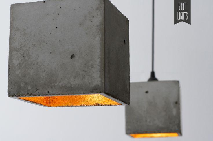 *[B1]*      Die Lampe ist aus schlichtem Beton in simpler kubischer Form gegossen.    Das Innere des Lampenschirms ist vergoldet und lässt das Licht