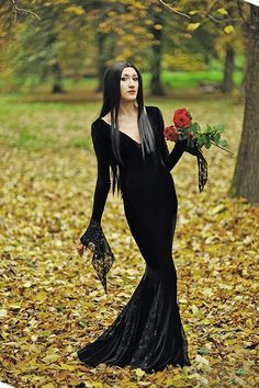 Combine a long black dress, red lips and sleek hair to become Morticia Addams.