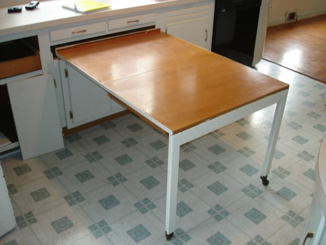 Great space saving idea. the built-in kitchen table shown left. The top of the table folds in half so that it fits under a regular size countertop. The 2 legs are on wheels so it rolls back under the counter. It provides a nice work area.