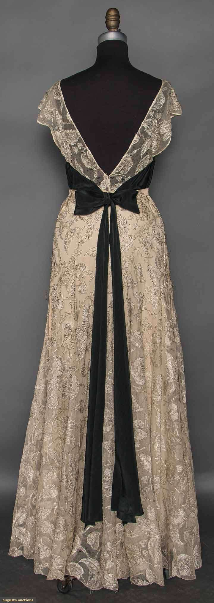 "CHANEL COUTURE LACE GOWN, c. 1935 (back view) White lace in overall foliage & blossom pattern, metallic silver thread embellishes lace motifs, sleeveless, V F&B neck, wide black silk charmeuse ribbon ties to CF bow continuing to long CB bow, attached lace belt, beige silk underslip, label ""Chanel"", tape ""26419"""