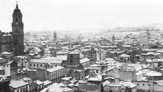 No he podido determinar la fecha en la que está tomada la foto antigua, pero vemos que la ciudad está nevada. He comprobado que ha habido dos grandes nevadas en la ciudad de Málaga, una en 1906 y otra el 3 de febrero de 1954. Supongamos que se trata del segundo caso, debido a que la calidad de la imagen es más de la segunda época que de la primera.  Las dos imágenes son prácticamente idénticas, sino fuera por el bloque de pisos de la izquierda y algunos otros que se encuentran en primer…