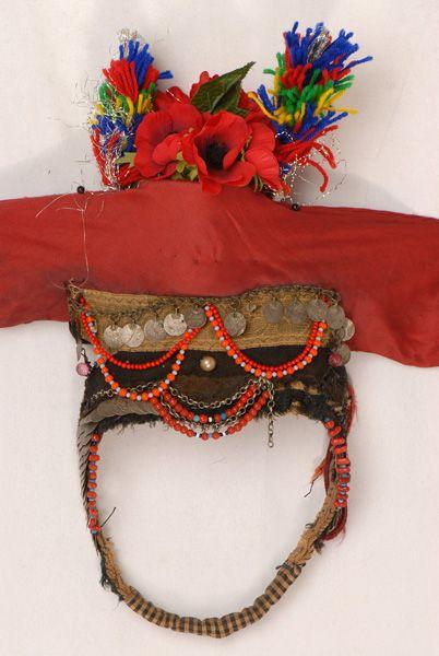 Το νυφικό κεφαλοκάλυμμα της Ορεινής Σερρών αποτελείται από πλήθος εξαρτημάτων. Ως βάση έχει το κουταλάκ, κυλινδρικό μεταλλικό κουτί, ντυμένο με υπόλευκο βαμβακερό ύφασμα. Το κουταλάκ φοριέται στην κορυφή του κεφαλιού και στερεώνεται, συνήθως, με δύο υποσιαγώνια, το γιορντάνι, που είναι χάντρινο και το ποντγκαρλέ, μια παραδένια αργυρή αλυσίδα. Εδώ υπάρχουν μόνο δύο τμήματα μαύρης φακαρόλας. αρχές 20ού αι.γιορτινό. Μακεδονία ΝομόςΣερρών
